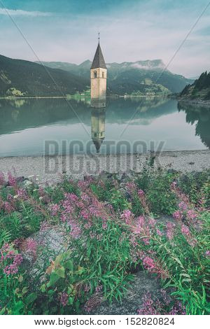 Beautiful view of the lake Resia. Famous tower in the water. Alps, Italy, Europe, toned like Instagram filter