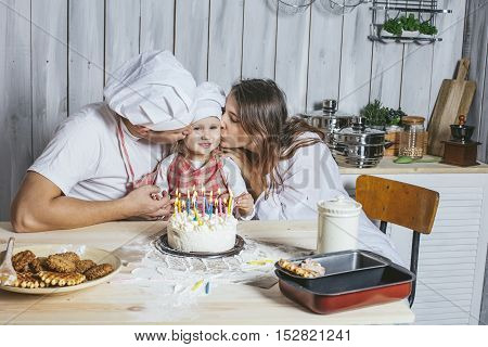 Family, Happy Daughter With Mom And Dad At Home In The Kitchen Laugh And Lit The Candles On The Birt