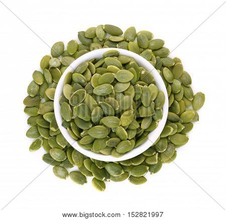 top view of pumpkin seeds in white bowl isolated on white