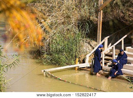 BETHABARA, ISRAEL - OCTOBER- 7, 2016: Pilgrims Catholic nuns on the banks of the Jordan River at the site of Jesus' baptism. Israel - 2016