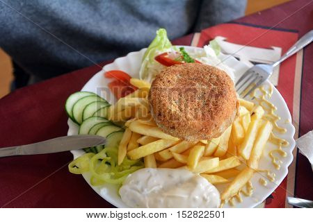 Breaded cheese with french fries and vegetables on a plate