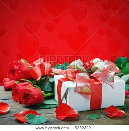 fresh red roses and a gift isolated on a red background with hearts