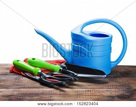garden tools lying on wooden table isolated on white background