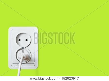 White electric socket on the green wall