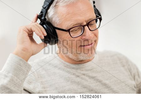 technology, people and lifestyle concept - close up of happy senior man in headphones listening to music at home