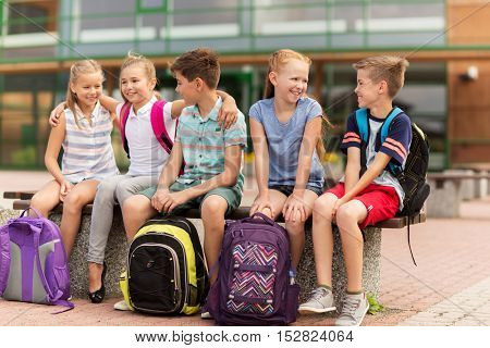 primary education, friendship, childhood, communication and people concept - group of happy elementary school students with backpacks sitting on bench and talking outdoors