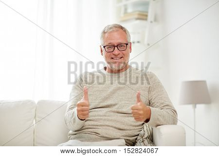 old age, gesture and people concept - smiling senior man in glasses sitting on sofa and showing thumbs up at home