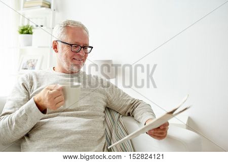 leisure, information, people and mass media concept - happy smiling senior man in glasses reading newspaper at home
