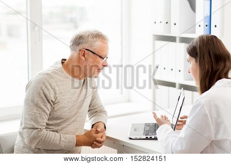 medicine, age, health care and people concept - senior man and doctor with laptop computer meeting in medical office at hospital