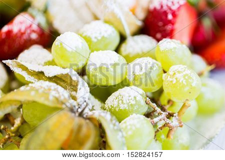 food, fruits, dessert and summer concept - close up of dish with sugared grapes