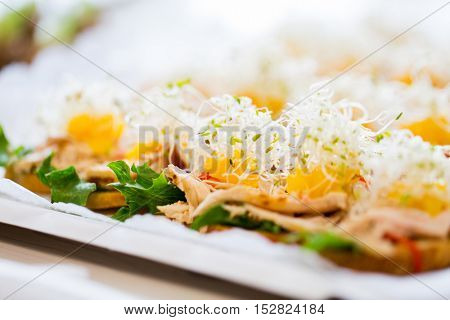 food, junk-food, catering and unhealthy eating concept - close up of canape or sandwiches on serving tray