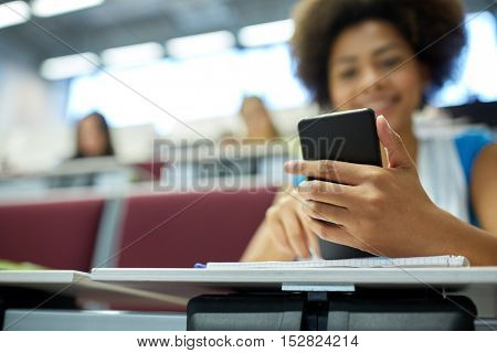 education, high school, university, learning and people concept - close up of happy african student girl with smartphone at lecture hall