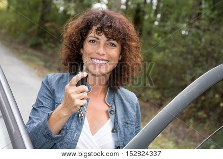 young smiling woman standing to the car taking key handover rent purchase