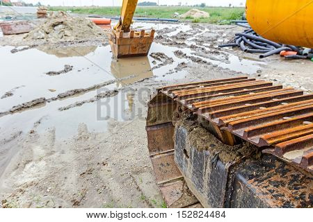 View under the arm of excavator. Reflection on water surface construction site after rain