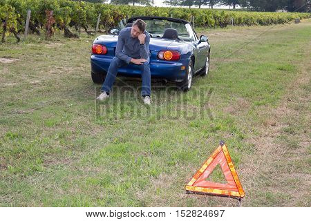 Triangle Warning Sign With Broken Down Car On Background