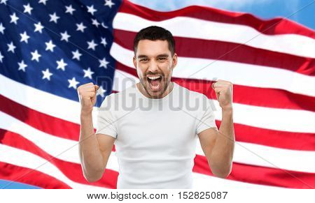 emotion, aggression, patriotism, gesture and people concept - angry young man showing fists and shouting over american flag