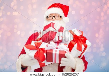 christmas, holidays and people concept - man in costume of santa claus with gift boxes over rose quartz and serenity lights background