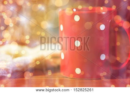 holidays, christmas, winter and drinks concept - red polka dot tea cup on wooden table over lights
