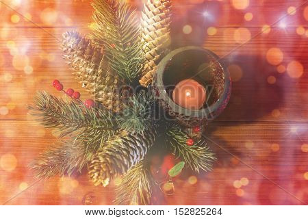 christmas, decoration, holidays and new year concept - close up of natural fir branch decoration and fir-cone and candle in lantern on wooden table over lights