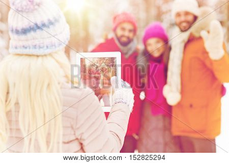 technology, season, friendship and people concept - close up of happy men and women taking picture with tablet pc computer in winter forest