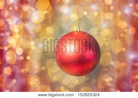 christmas, decoration, holidays concept - close up of red shiny ball over golden lights background