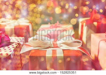 christmas, holidays, presents, new year and celebration concept - close up of gift boxes over christmas lights
