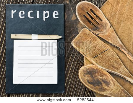 Wooden kitchen utensils and a notepad to write a recipe