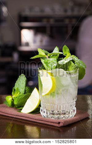 green alcoholic cocktail in transparent glass with lemon and mint