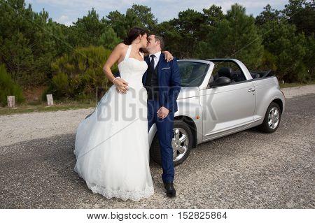 Happy Newlywed Couple Posing Near Convertible Car