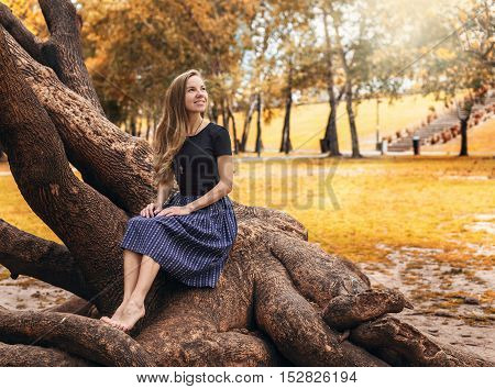 Beautiful caucasian girl sitting on the tree in the autumn park looking at the sun and smiling. Happy thanksgiving.