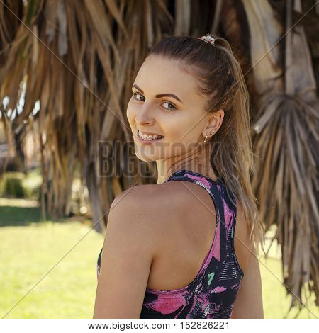 Beautiful caucasian sporty girl turn back and smile on the beach with palm leafs on the background.