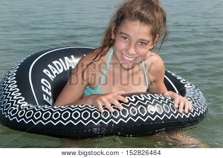 Relaxing Young Girl In A Black Buoy At The Sea