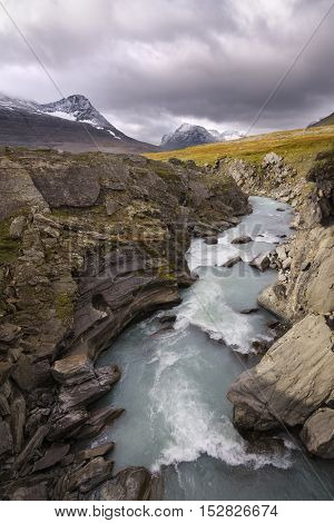 River of melt water flowing in beautiful autumn mountain landscape
