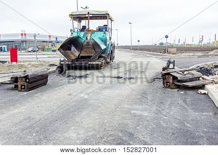 Dirty metal parts are dismantled from asphalting machine. Asphalt spreader out of order