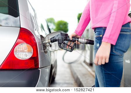 Closeup of woman pumping gasoline fuel in car at gas station. Petrol or gasoline being pumped into a motor vehicle car.