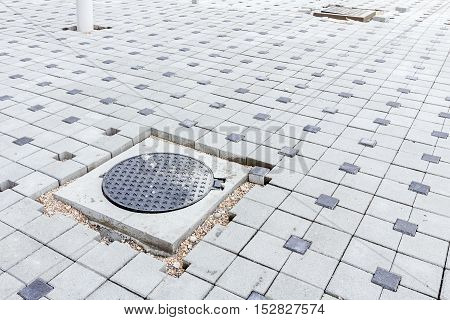 New metal cover over concrete manhole is unfinished on tiled walkway.