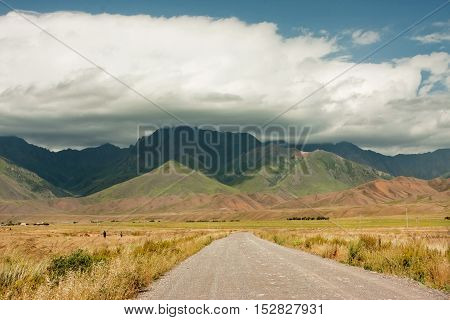 Asphalt road leading to the high mountains covered by thunderclouds before rain at the sunny spring day