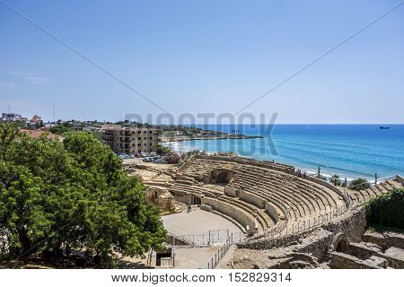 Ruins of roman amphitheater at Tarragona in Spain and the mediterranean sea on the background