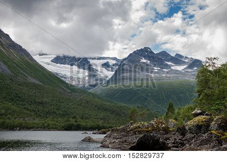 Cloudy Norwegian Mountains with Lake. Beautiful snowy mountains in Norway on a cloudy day