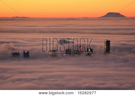 VANCOUVER - JANUARY 18, 2009: Morning sunrise on the city of Vancouver covered in thick fog, January 18, 2009. Only the tops of the tallest buildings are visible.