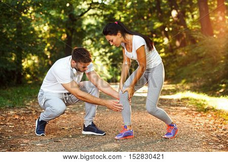 Man helps a woman due to knee injury after running
