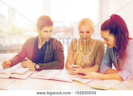 school, technology, internet and education concept - group of smiling students with smartphones and notebooks at school
