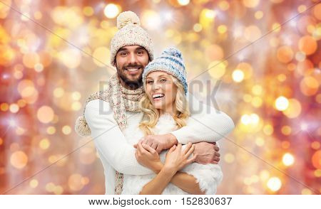 winter, holidays, couple, christmas and people concept - smiling man and woman in hats and scarf hugging over lights background
