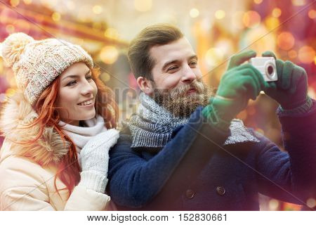 holidays, winter, christmas, technology and people concept - happy couple of tourists in warm clothes taking picture with camera in old town