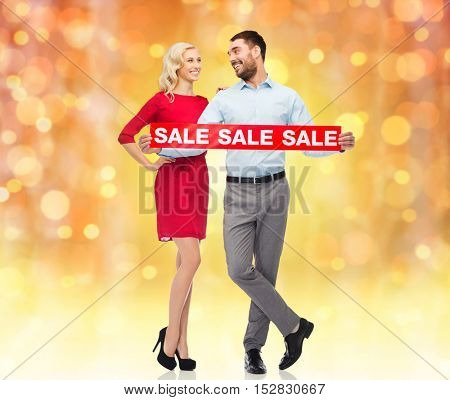 people, christmas, sale, discount and holidays concept - happy couple with red sale sign looking at each other over lights background