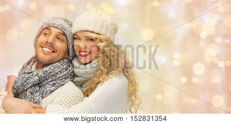 people, christmas, holidays and new year concept - happy family couple in winter clothes hugging over holidays lights background