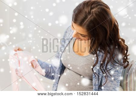 winter, christmas , pregnancy and people concept - close up of happy woman holding and looking at pink baby girls bodysuit at home over snow
