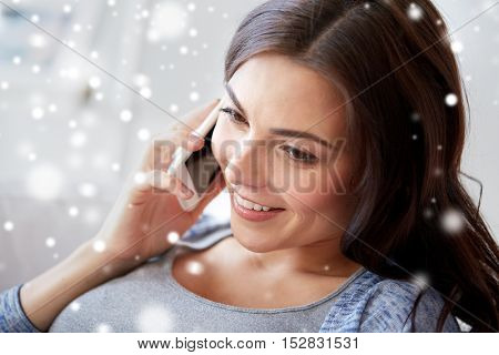 people, technology, winter, christmas and communication concept - happy young woman calling on smartphone at home over snow