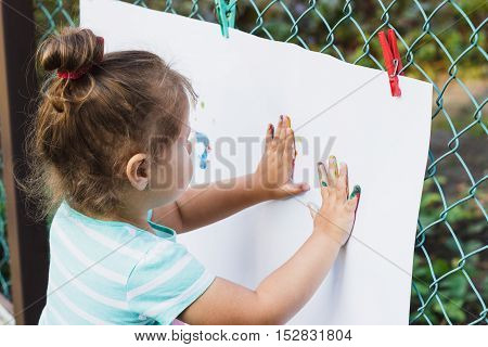 Small Girl Draws Painted Hands