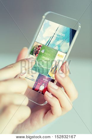 business, technology, internet and people concept - close up of woman hand holding and showing transparent smartphone with news web pages on screen